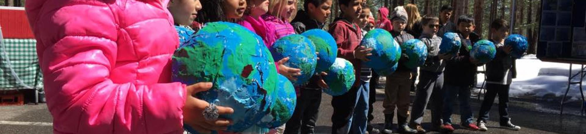 A line of kids hold paper mache Earths at a past South Lake Tahoe Earth Day Celebration